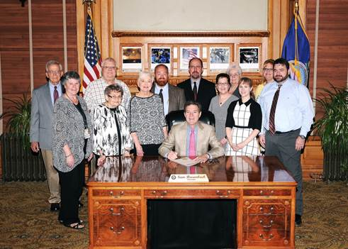 Governor Brownback signs Adult Abuse Awareness Proclamation.
