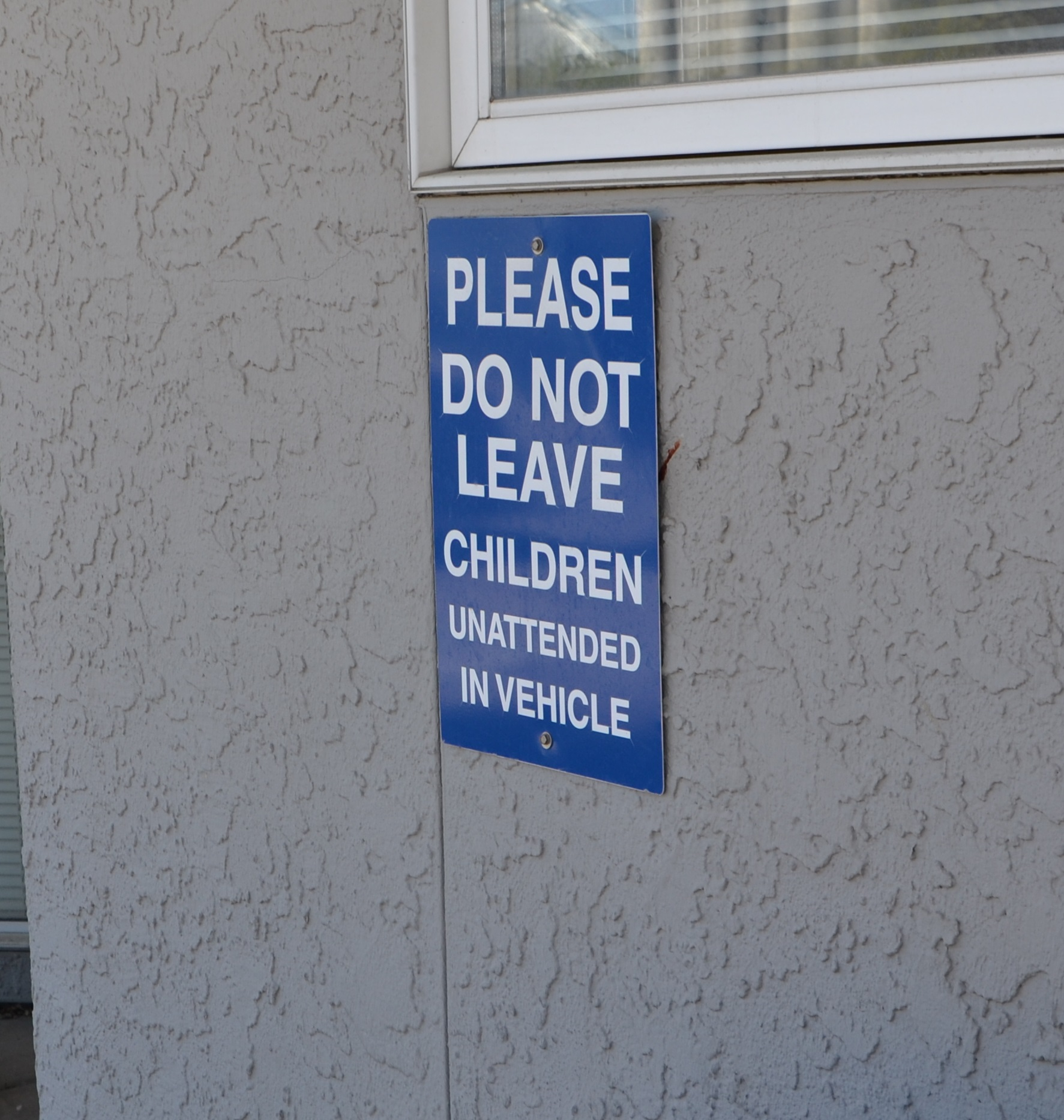 "Picture of a sign outside a building that reads ""Please do not leave children unattended in vehicle"""