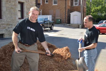 Secretary Siedlecki and Legislative Director Gary Haulmark spread new mulch over a playground at the school.