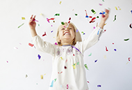 Photo of young girl smiling, looking up with arms outstretched, as colorful confetti falls from above.